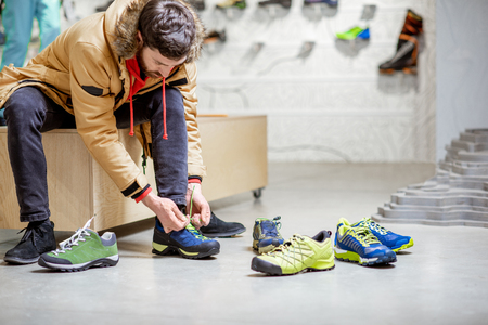 Man in winter jacket trying shoes for mountain hiking sitting in the fitting room of the modern sports shop