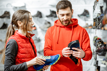 Photo pour Mam and woman in red sports clothes choosing trail shoes for hiking standing near the showacase of the modern sports shop - image libre de droit