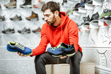Foto de Man choosing trail shoes for hiking sitting in the fitting room of the modern sports shop - Imagen libre de derechos