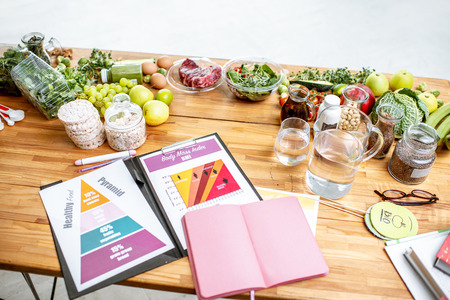 Nutritionists working place with drawings on the topic of healthy eating, empty notebook and different products on the table
