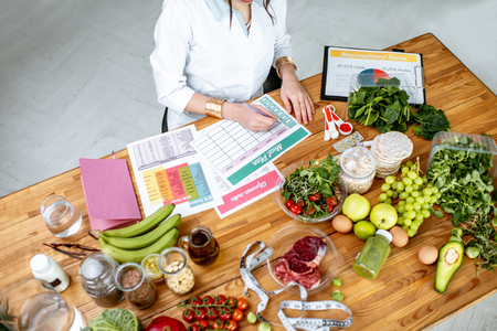 Dietitian writing a diet plan, view from above on the table with different healthy products and drawings on the topic of healthy eating