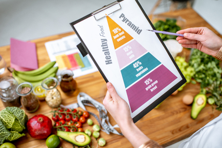 Photo pour Holding schematic meal plan for diet with various healthy products on the background - image libre de droit