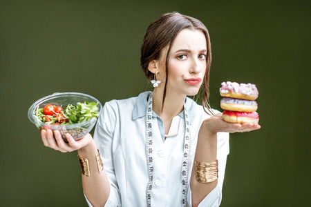 Foto de Young woman nutritionist looking on the donuts with sad emotions choosing between salad and unhealthy dessert on the green background - Imagen libre de derechos