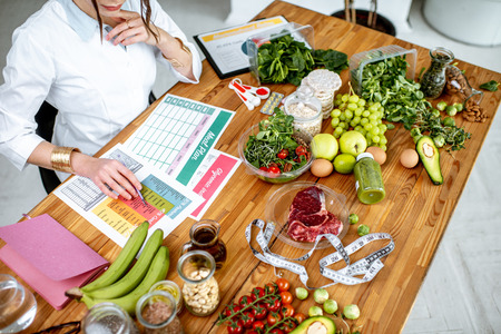 Foto de Dietitian writing a diet plan, view from above on the table with different healthy products and drawings on the topic of healthy eating - Imagen libre de derechos