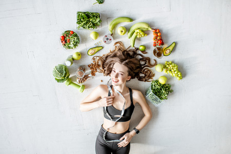 Photo pour Beauty portrait of a sports woman surrounded by various healthy food lying on the floor. Healthy eating and sports lifestyle concept - image libre de droit
