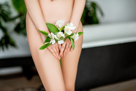 Foto de Beautiful womans body with flower covering her intimate place in the bathroom - Imagen libre de derechos