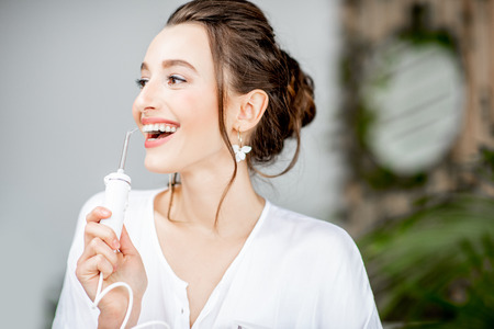 Photo pour Portrait of a beautiful woman with shiny smile holding irrigator tool for teeth cleaning in the bathroom - image libre de droit