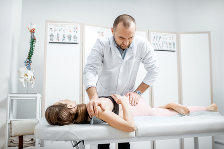 Photo pour Professional senior physiotherapist doing manual treatment to a young woman with spine problems in the cabinet of rehabilitation clinic - image libre de droit