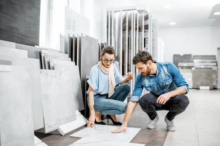 Foto de Beautiful young couple choosing big granite tiles for their house repairment in the building shop - Imagen libre de derechos