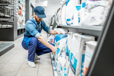 Foto de Workman in blue overalls taking a bag with construction mixture, buying materials for repairing in the building supermarket - Imagen libre de derechos
