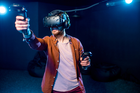 Foto de Man playing game using virtual reality headset and gamepads in the dark room of the playing club - Imagen libre de derechos