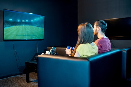 Photo pour Young couple playing football game with gaming console sitting on the couch at the playing club, back view with tv screen - image libre de droit