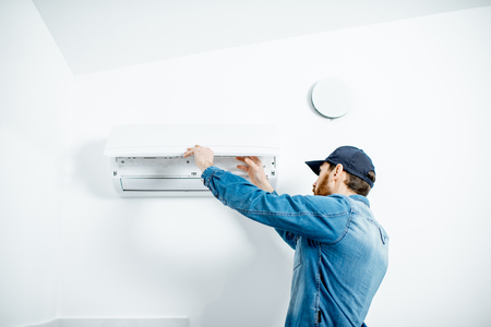 Photo pour Repairman in blue workwear serving the air conditioner changing filter on the white wall background - image libre de droit