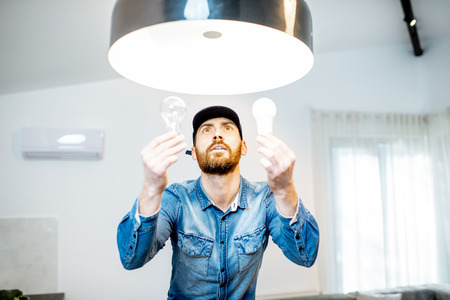 Photo for Handyman choosing between energy save and cheap incandescent lamp while changing light in the appartment - Royalty Free Image