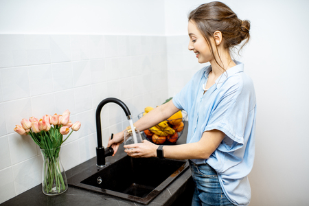 Foto de Woman filling glass with tap water for drinking on the kitchen - Imagen libre de derechos