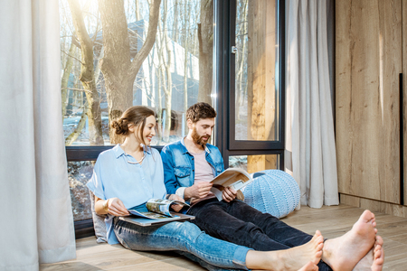 Foto de Happy couple sitting together on the floor near the window with beautiful view, reading some magazines and relaxing at home - Imagen libre de derechos