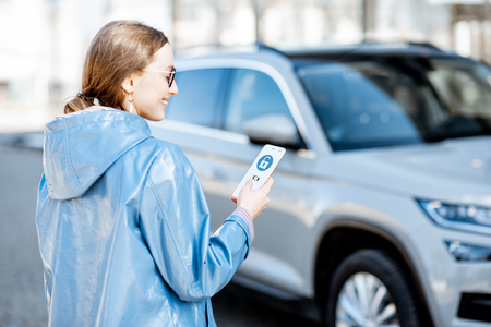 Foto de Woman unlocking car using mobile application on a smart phone. Concept of a remote control and car protection through the internet - Imagen libre de derechos