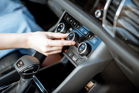 Photo pour Woman turning wheel of the air conditioner in the car, close-up view - image libre de droit