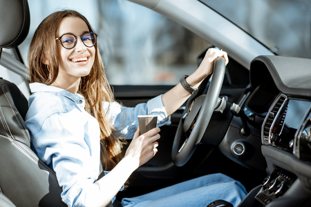 Photo pour Portrait of a young and cheerful woman with coffee cup driving luxury car in the city - image libre de droit