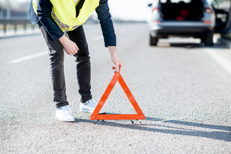 Foto de Man in road vest putting emergency triangle sign on the highway with broken car on the background, close-up view - Imagen libre de derechos