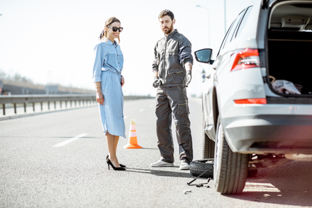 Photo pour Road assistance worker in uniform with young woman standing near the broken car on the highway - image libre de droit