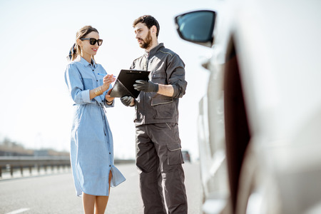 Photo for Road assistance worker signing some documents with woman near the broken car on the highway - Royalty Free Image