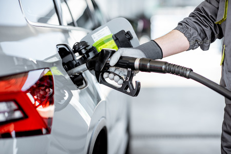 Photo for Gas station worker refueling car with gasoline, close-up view focused on the filling gun - Royalty Free Image