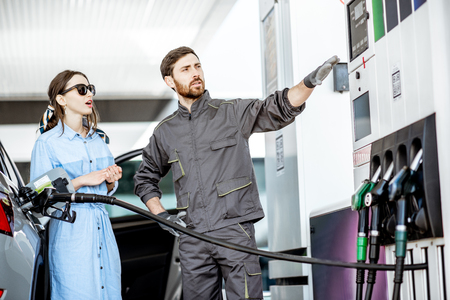 Photo pour Young woman client with gas station worker refueling car at the gas station - image libre de droit