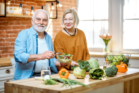 Foto de Cheerful senior couple eating salad standing together with healthy food on the kitchen at home. Concept of healthy nutrition in older age - Imagen libre de derechos