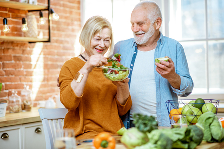 Foto de Portrait of a cheerful senior couple with salad and healthy food on the kitchen at home. Concept of healthy nutrition in older age - Imagen libre de derechos