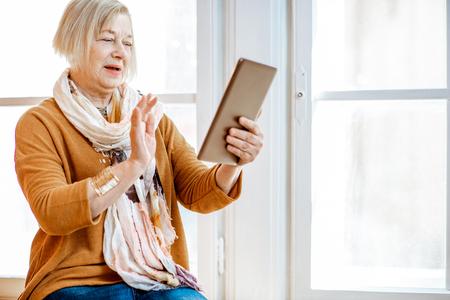 Photo pour Beautiful senior woman using digital tablet sitting near the window at home - image libre de droit