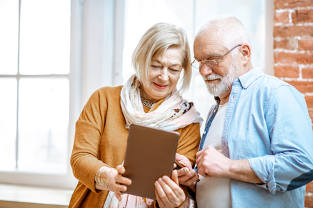 Photo pour Beautiful senior couple using digital tablet standing together near the window at home - image libre de droit