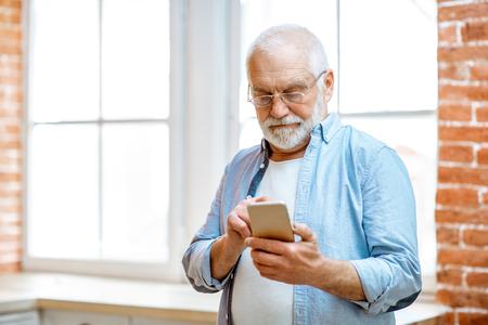 Foto de Cheerful senior grandfather using phone standing near the window at home - Imagen libre de derechos