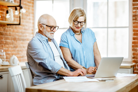 Foto de Beautiful senior couple in blue shirts working together with laptop on the kitchen at home - Imagen libre de derechos