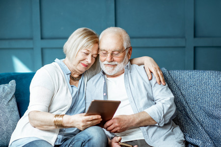 Photo pour Lovely senior couple dressed casually using digital tablet while sitting together on the comfortable couch at home - image libre de droit