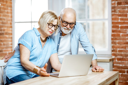 Photo pour Happy senior couple shopping online using credit card and laptop at home - image libre de droit