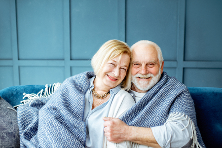 Photo for Portrait of a lovely senior couple feeling cozy and warm, sitting wrapped with plaid on the couch at home - Royalty Free Image