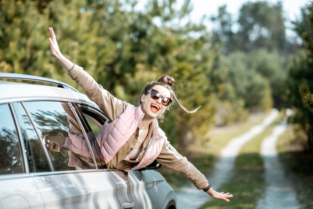 Photo pour Young woman enjoying the trip, looking out the car window on a picturesque road in the woods - image libre de droit