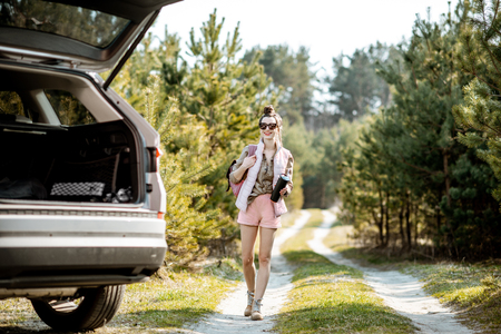 Photo pour Young woman traveler walking on a picturesque road, traveling by car in the forest - image libre de droit