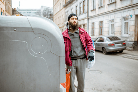 Photo for Portrait of a homeless depressed beggar standing with bags near the trash containers in the city. Concept of poverty and unemployment - Royalty Free Image