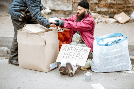 Photo for Homeless depressed beggars with bags and some food on the street on the ragged wall background. Concept of social poverty - Royalty Free Image