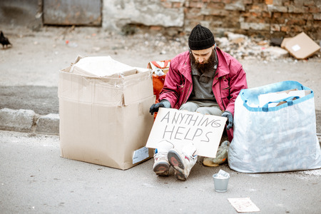Photo for Homeless depressed beggar sitting with bags and cardboards on the street on the ragged wall background. Concept of social poverty - Royalty Free Image