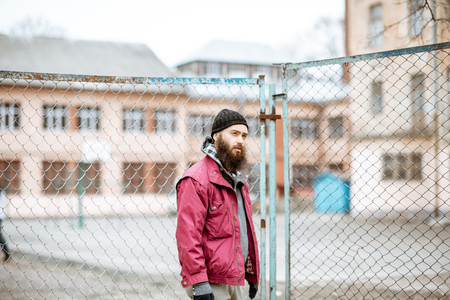 Photo for Portrait of a depressed homeless beggar or prisoner standing near the old metal fence outdoors - Royalty Free Image