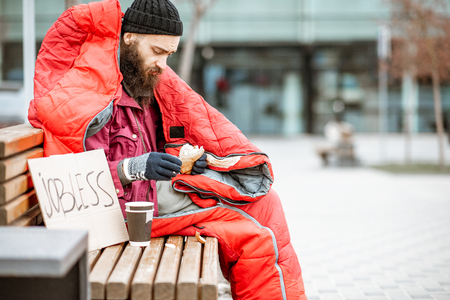 Photo for Depressed homeless beggar eating bread while sitting wrapped with sleeping bag on the bench near the business center - Royalty Free Image