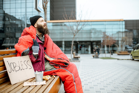 Photo for Homeless and jobless beggar sitting on the bench wrapped with sleeping bag begging money near the business center - Royalty Free Image