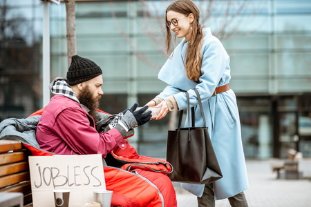 Photo for Smiling woman helping homeless beggar giving some food outdoors. Concept of helping poor people - Royalty Free Image