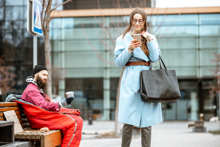 Photo for Homeless begging money while sitting on the bench with passing by businesswoman near the business center - Royalty Free Image