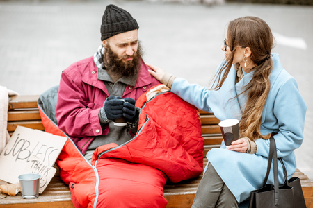 Photo for Homeless beggar with young woman listening to his sad story while sitting together on the bench outdoors. Concept of human understanding - Royalty Free Image