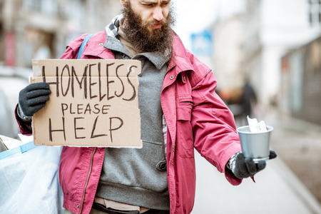 Photo for Portrait of a depressed homeless beggar with cardboard begging some money on the street in the city - Royalty Free Image