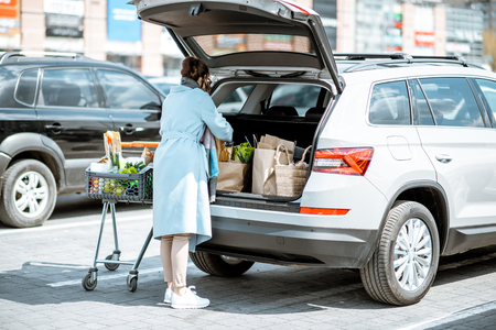 Photo pour Woman packing food bought in the supermarket into the car trunk on the parking - image libre de droit